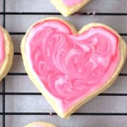 einkorn sugar cookie with pink glaze frosting on a cooking rack